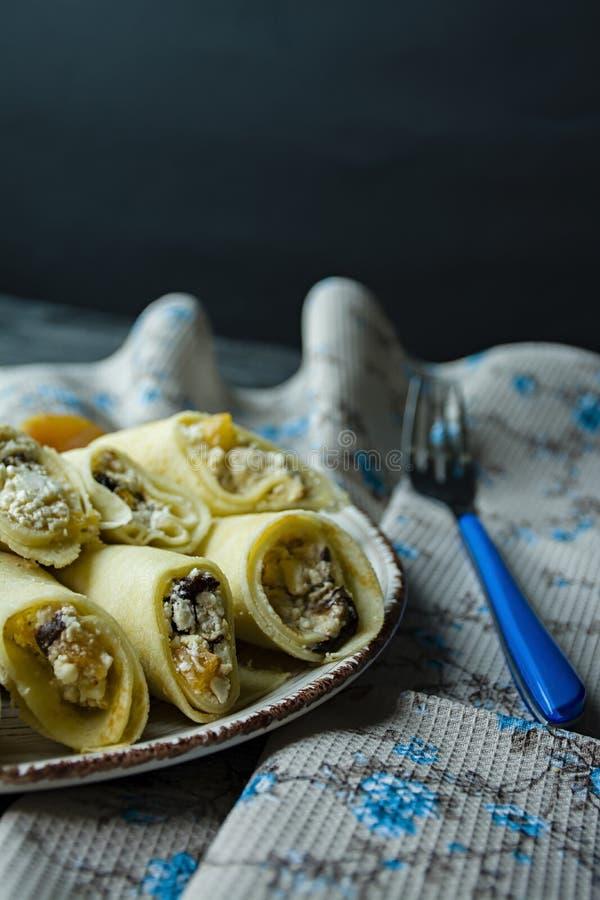 Pancake con la ricotta, le prugne, le albicocche secche e l'uva passa Vista laterale Priorit? bassa di legno scura immagini stock