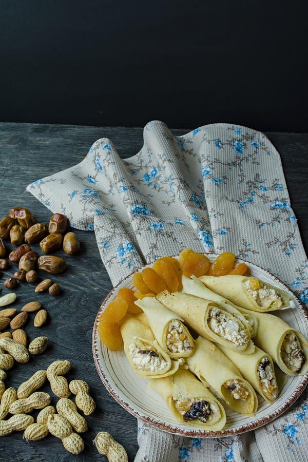 Pancake con la ricotta, le prugne, le albicocche secche e l'uva passa Vista laterale Priorit? bassa di legno scura immagine stock libera da diritti