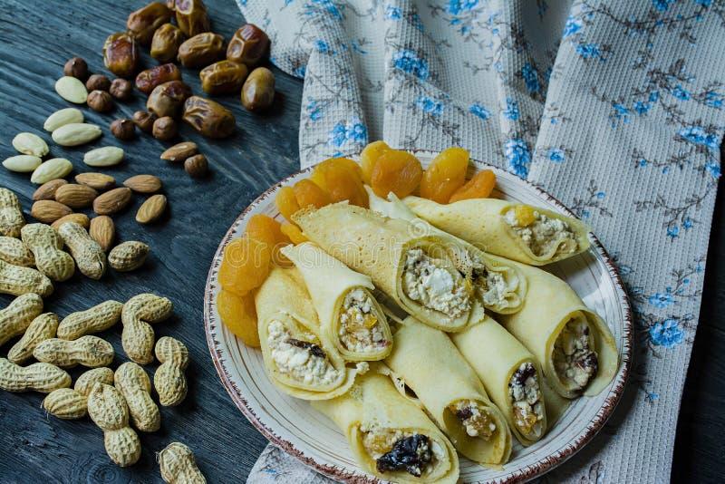 Pancake con la ricotta, le prugne, le albicocche secche e l'uva passa Vista laterale Priorit? bassa di legno scura immagini stock libere da diritti