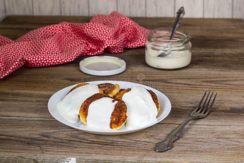 Pancake con la ricotta, panna acida in un piatto bianco immagini stock libere da diritti