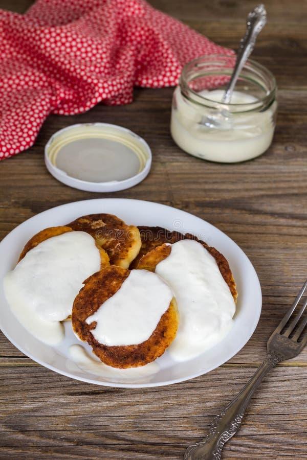 Pancake con la ricotta, panna acida in un piatto bianco immagini stock