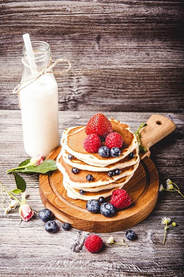 Pancake con le bacche di estate e la bottiglia fresche di latte fotografia stock