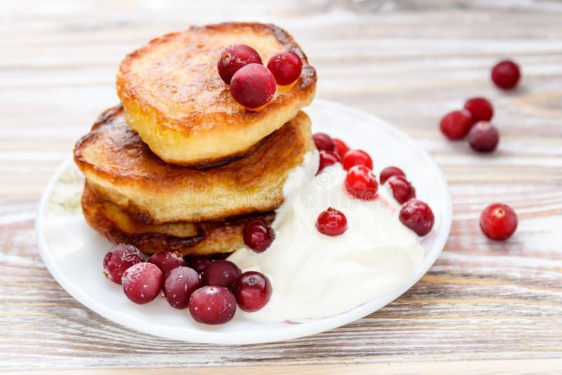 Pancake con le bacche e la panna acida su un piatto Cottage di estate delle squisitezze russe fotografia stock