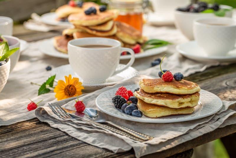 Pancake con le bacche ed il miele freschi nel giardino di estate fotografia stock libera da diritti