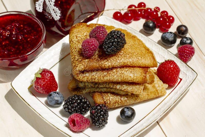 Pancake con le bacche, il burro ed il tè in una tazza bianca della porcellana Prima colazione sana di estate, Russo classico casa fotografie stock
