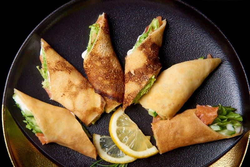 Pancake con le fette del limone e del materiale da otturazione su un piatto immagine stock
