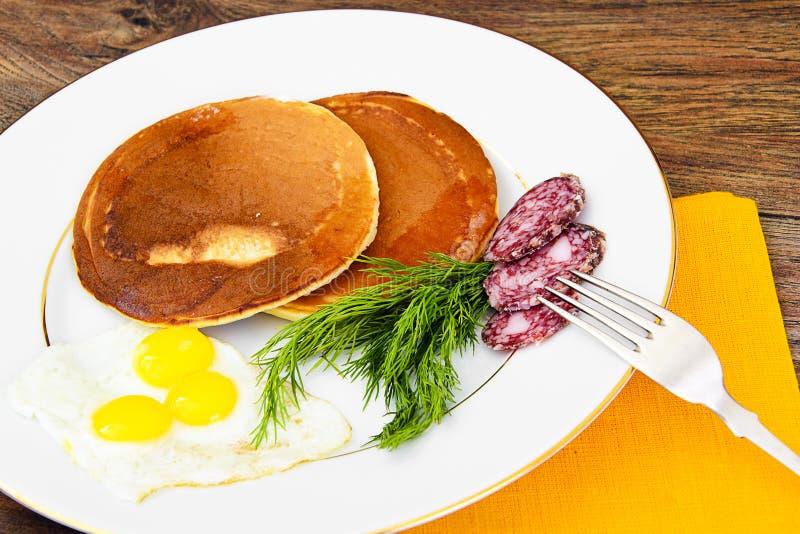 Pancake con le uova di quaglia, carni fredde, cucchiaio della pasticceria con il Ca nero immagine stock libera da diritti