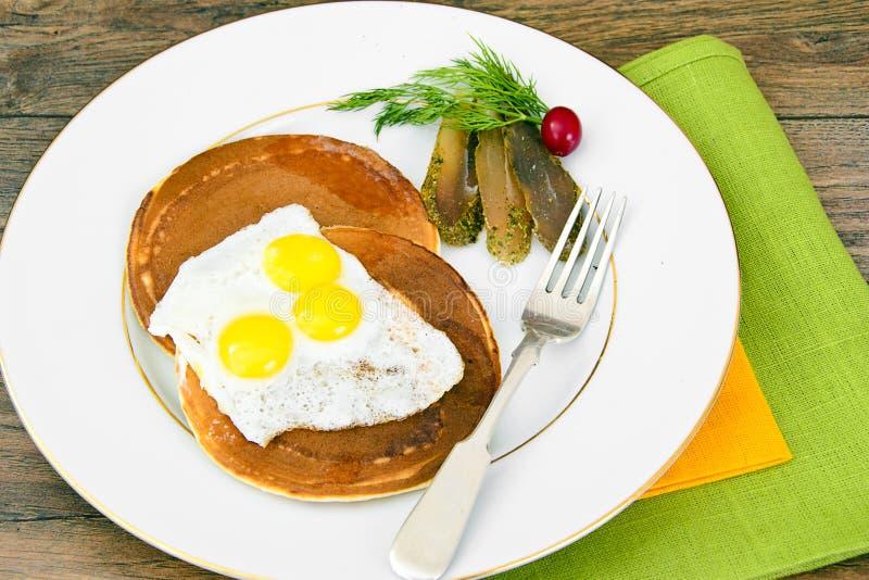 Pancake con le uova di quaglia, carni fredde, cucchiaio della pasticceria con il Ca nero immagini stock