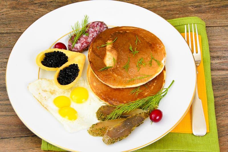 Pancake con le uova di quaglia, carni fredde, cucchiaio della pasticceria con il Ca nero fotografia stock