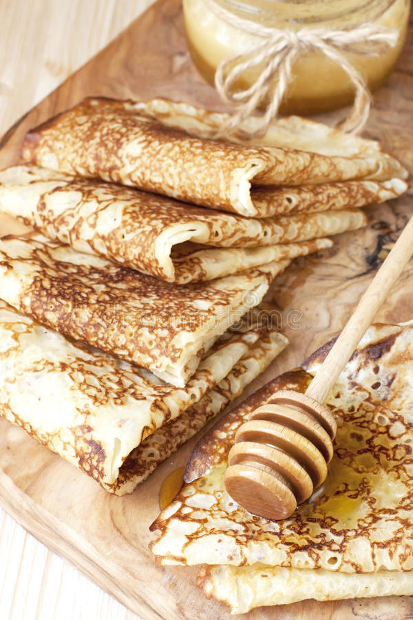 Pancake con miele sul bordo di legno fotografie stock