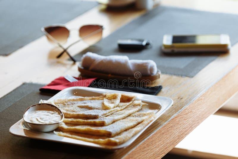 Pancake con panna acida sul piatto quadrato bianco sulla tavola immagine stock libera da diritti