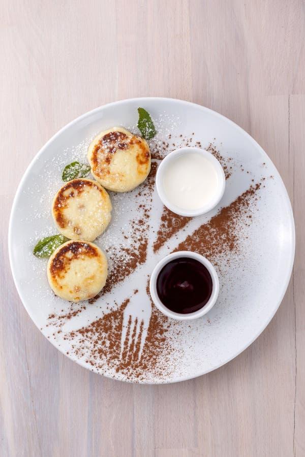 Pancake del formaggio con l'inceppamento e la panna acida del ribes su una vista superiore del piatto fotografia stock