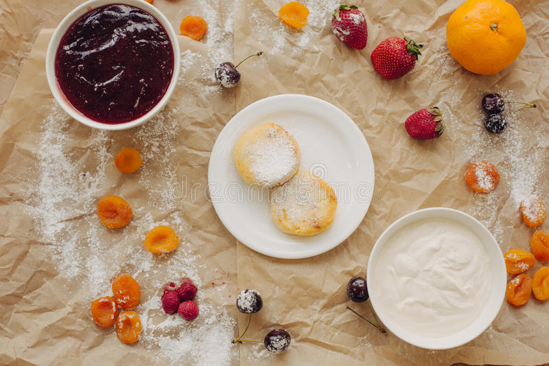 Pancake del formaggio con panna acida sul fondo della pergamena, disposizione piana fotografie stock libere da diritti