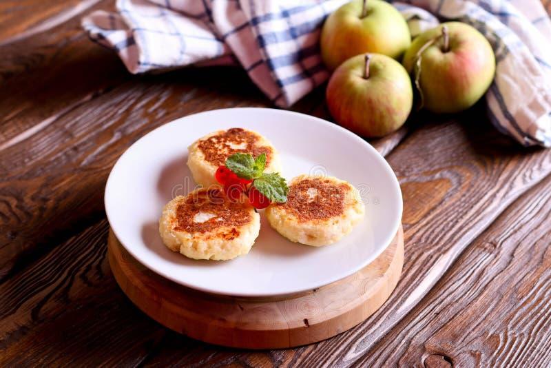 Pancake del formaggio, syrniki con il ribes su un piatto bianco fotografia stock