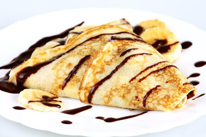 Pancake del primo piano con le banane ed il cioccolato immagine stock