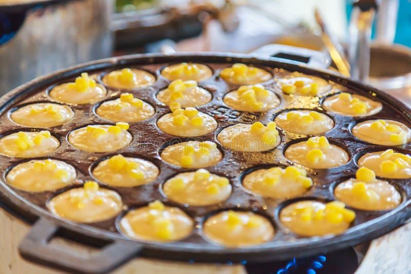 Pancake del riso della noce di cocco di Khanom Khrok, dessert tailandese tradizionale del pancake del budino, pronto mescolando l fotografia stock