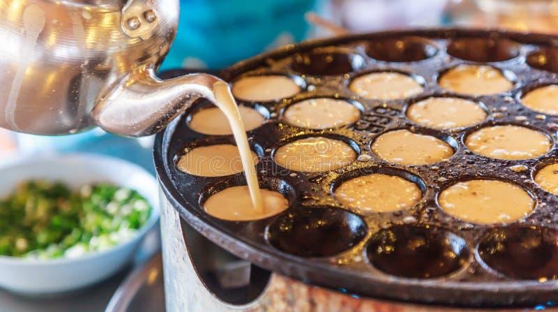 Pancake del riso della noce di cocco di Khanom Khrok, dessert tailandese tradizionale del pancake del budino, pronto mescolando l fotografia stock libera da diritti