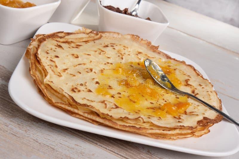 Pancake deliziosi con inceppamento arancio immagine stock