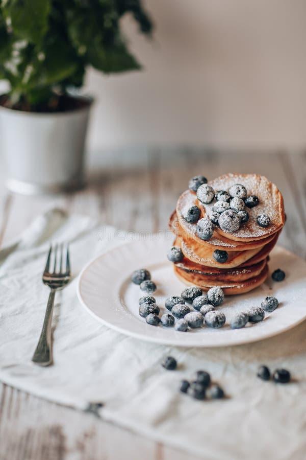 Pancake dell'avena della banana con i mirtilli su un piatto bianco fotografia stock libera da diritti