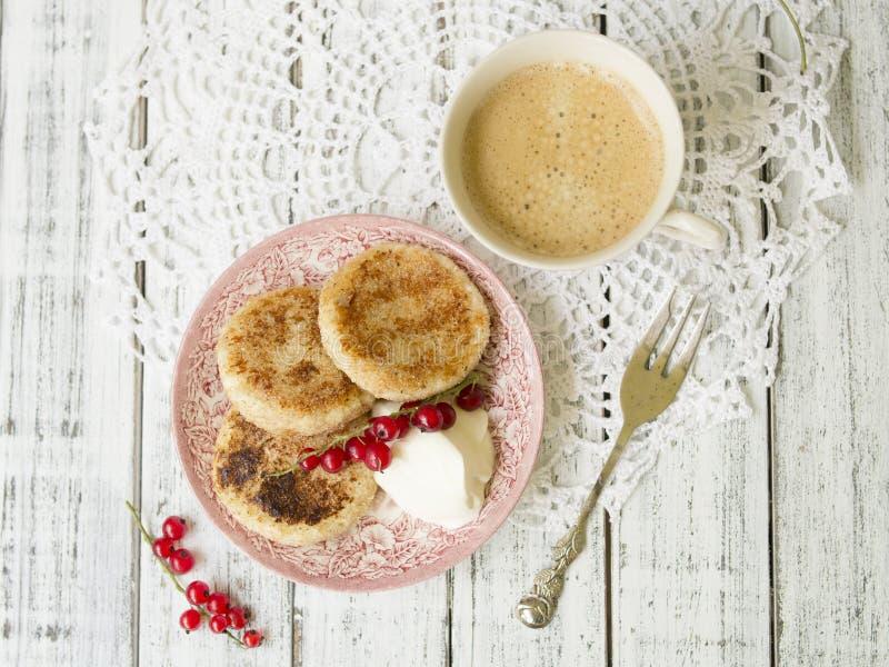Pancake della ricotta con le bacche e la panna acida, tazza di caffè nero, prima colazione saporita fotografia stock