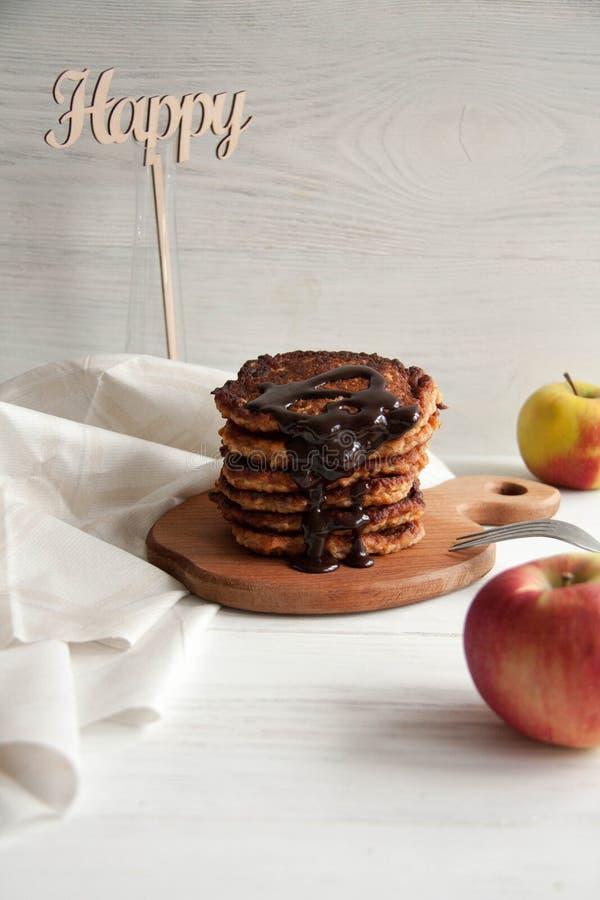 Pancake di Apple con cioccolato che si trova su un bordo di legno marrone immagine stock libera da diritti