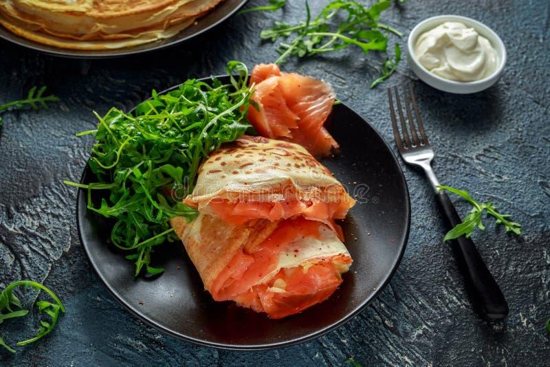 Pancake di crêpe con il salmone affumicato e l'insalata di razzo selvaggia immagini stock libere da diritti