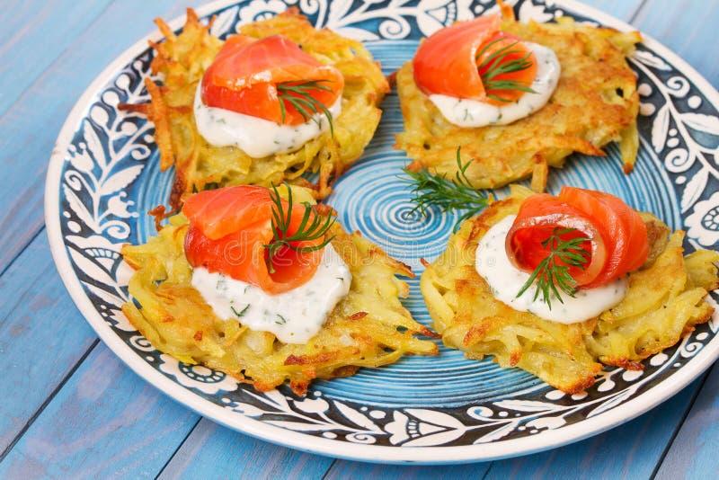 Pancake di patata con il salmone Frittelle di verdure con il pesce Latkes su un piatto fotografia stock
