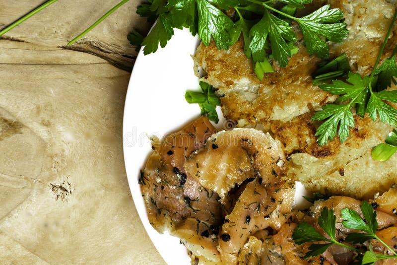 Pancake di patata con il salmone Frittelle di verdure con il pesce, pepe, Latkes del prezzemolo su un piatto fotografia stock libera da diritti
