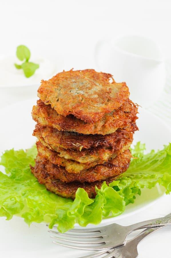 Pancake di patata con le foglie dell'insalata immagini stock