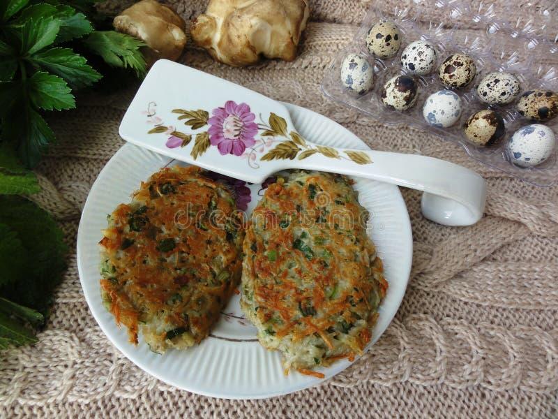 Pancake di patate dell'ortica di Artishok con le uova di quaglia immagini stock libere da diritti