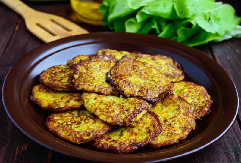 Pancake dorati dallo zucchini su un piatto dell'argilla fotografia stock libera da diritti