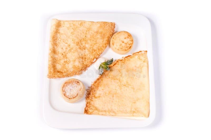 Pancake e frittelle con panna acida in un piatto rettangolare bianco su un fondo bianco fotografia stock libera da diritti