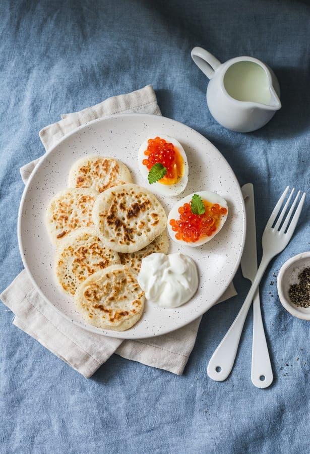 Pancake e uova sode acidi della pasta con il caviale rosso - prima colazione deliziosa, brunch su un fondo blu immagine stock libera da diritti