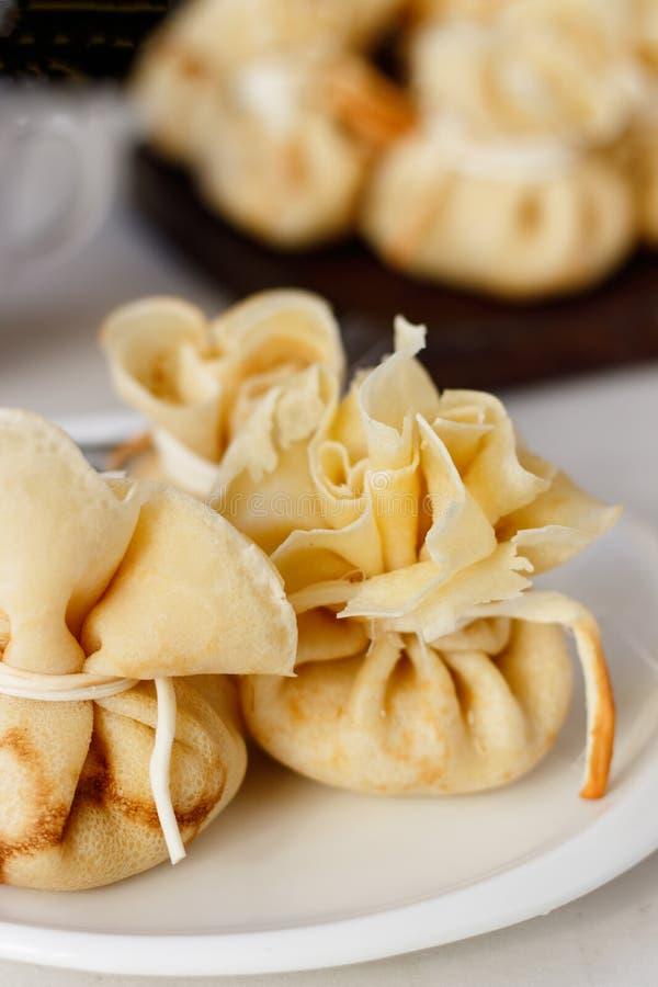 Pancake farciti con una borsa su un piatto bianco con il materiale da otturazione della carne legato con formaggio immagini stock