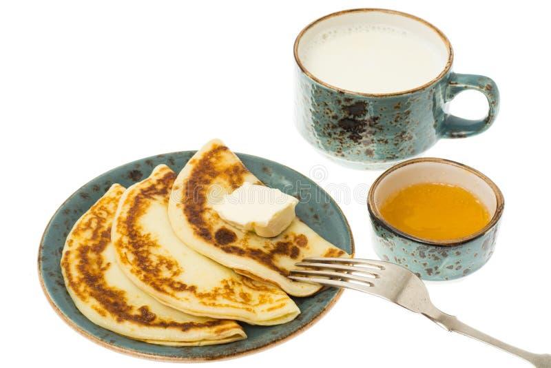 Pancake fritti saporiti con latte in tazza fotografie stock libere da diritti