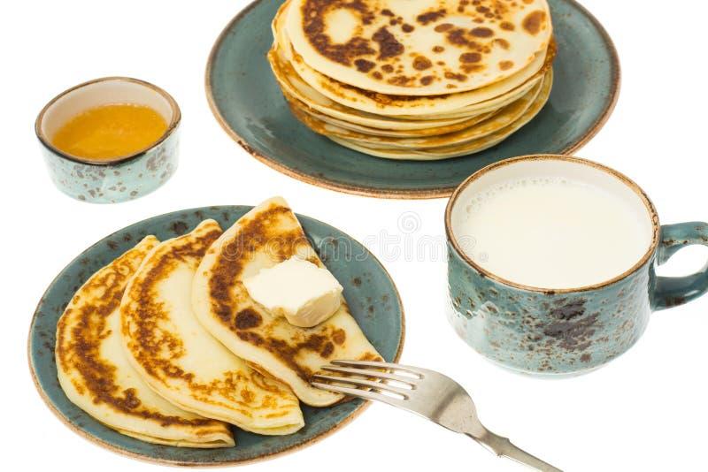 Pancake fritti saporiti con latte in tazza fotografia stock libera da diritti