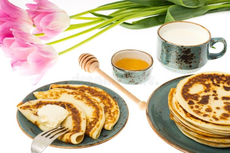 Pancake fritti saporiti con latte in tazza immagini stock