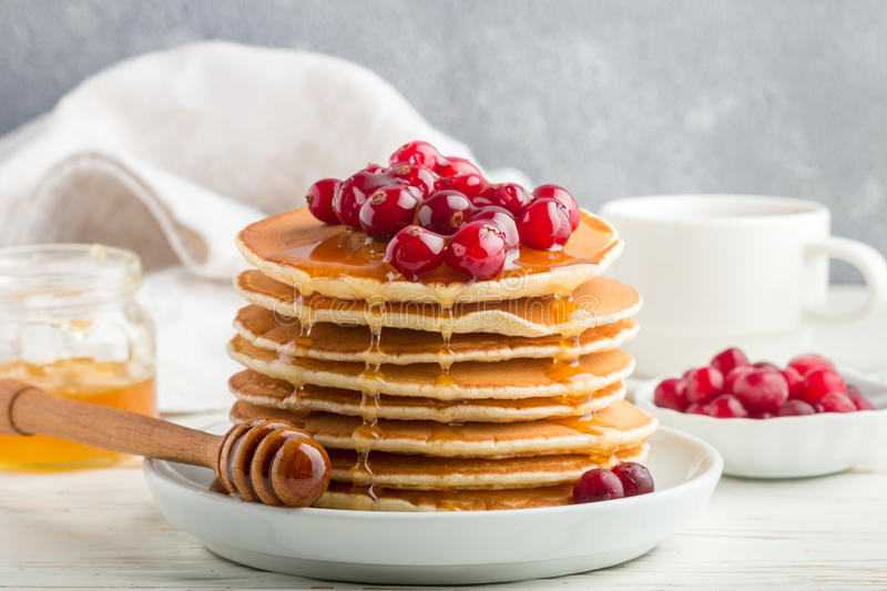 Pancake with honey and fresh berries. Cranberry, cowberry. Gourmet Breakfast. Selective focus royalty free stock images