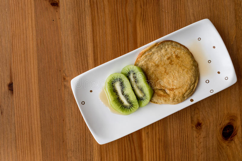 Pancake with kiwi and maple syrup made with organic flour copy. Space. homemade product stock photography
