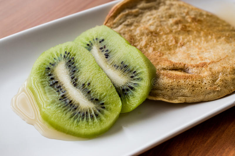 Pancake with kiwi and maple syrup made with organic flour. Homemade product stock image
