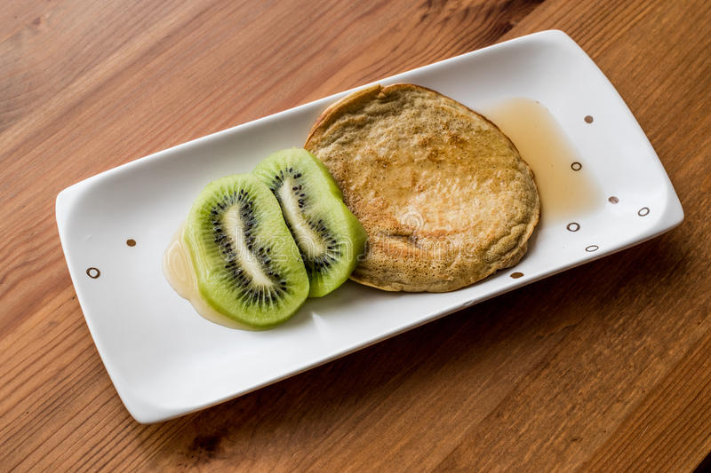 Pancake with kiwi and maple syrup made with organic flour. Homemade product stock photography