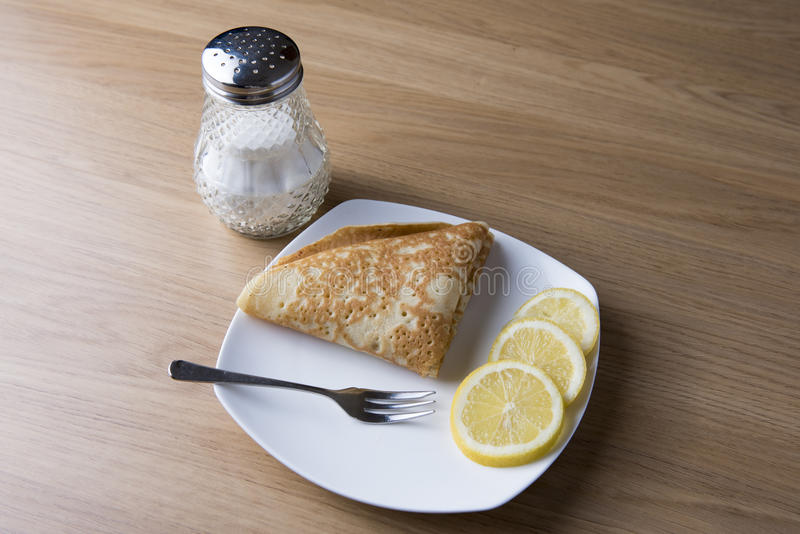 A pancake with lemon and sugar. A pancake on a white place with slices of lemon and a sugar dispenser royalty free stock photo