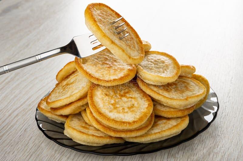 Pancake pendurado no garfo acima do monte de panquecas frias em prato em mesa de madeira fotos de stock royalty free