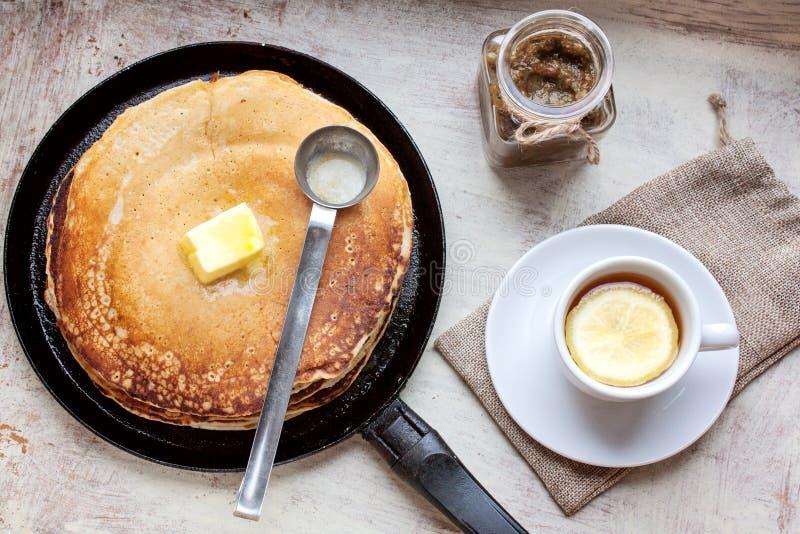 Pancake, petrolio, inceppamento e tè con un limone immagine stock