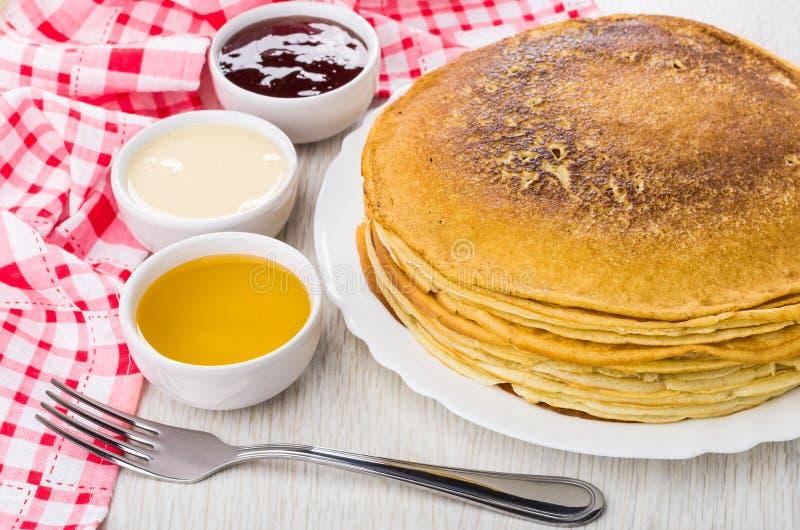 Pancake in piatto, inceppamento di fragola, miele, latte condensato, forcella, n fotografia stock