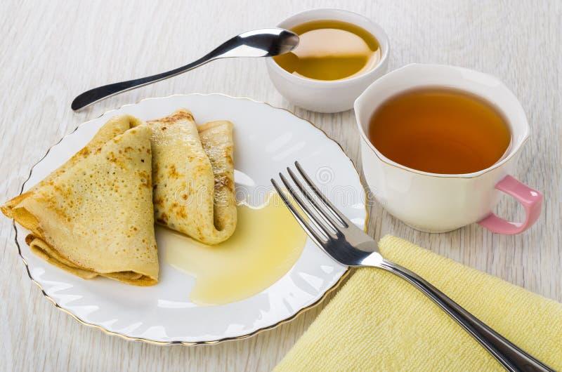 Pancake piegati con miele, cucchiaino, ciotola con miele, tovagliolo, t fotografie stock