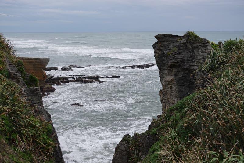 Punakaiki rocks and Tasman Sea on West Coast of New Zealand. Pancake rocks in Tasman Sea in Punakaki on the South Island of New Zealand on a winter day royalty free stock photos