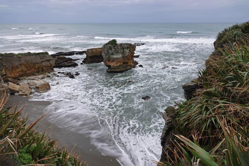 Punakaiki rocks and Tasman Sea on West Coast of New Zealand. Pancake rocks in Tasman Sea on the way to Punakaki on the South Island of New Zealand on a winter stock photo