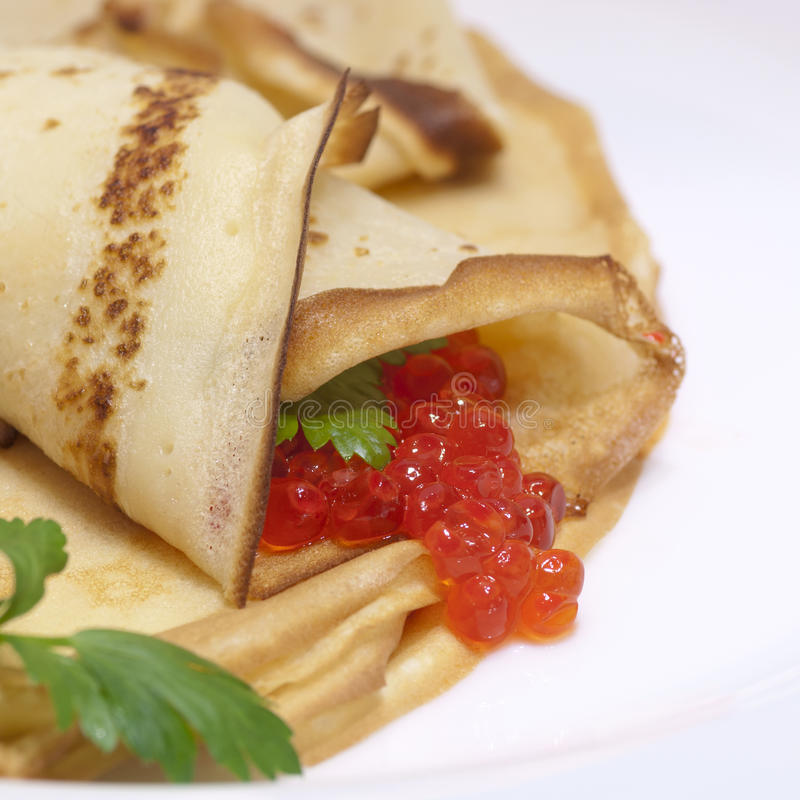 Pancake roll with red caviar stock image