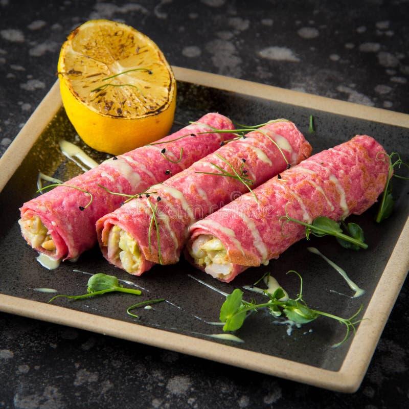 Pancake rosa farciti con il materiale da otturazione, la salsa ed il limone dei frutti di mare Aperitivo russo, alimento delizios fotografia stock